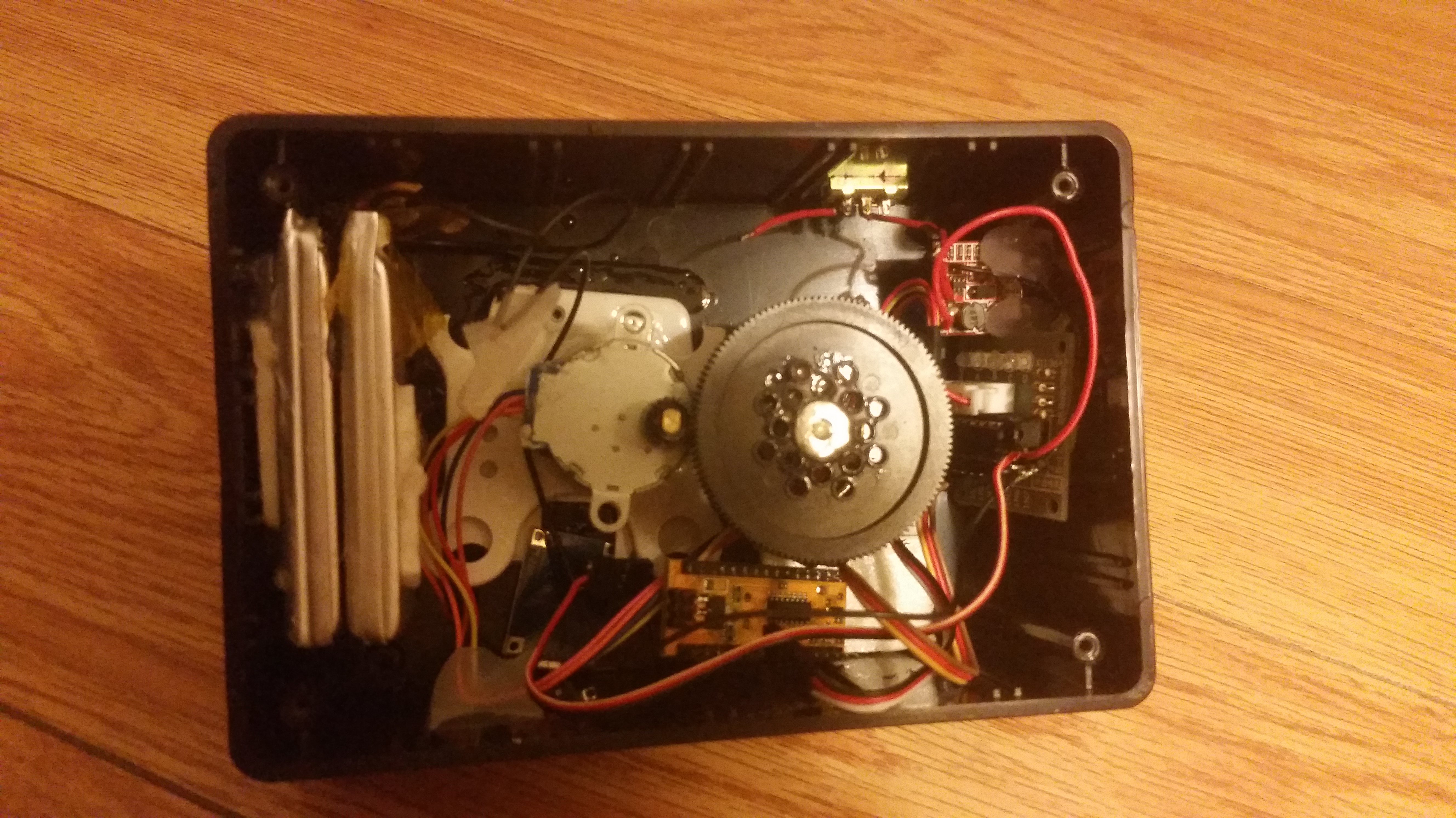 Internals of the time lapse panner, showing gears, stepper motor, battery, and Arduino