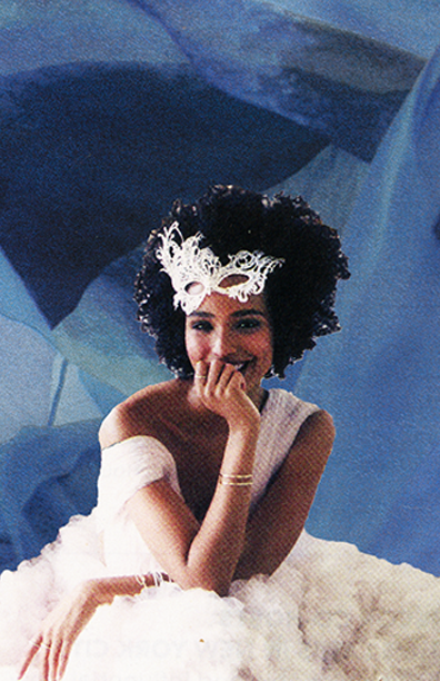 Woman smiling sitting down with a white dress on and a background that looks like chiffon.