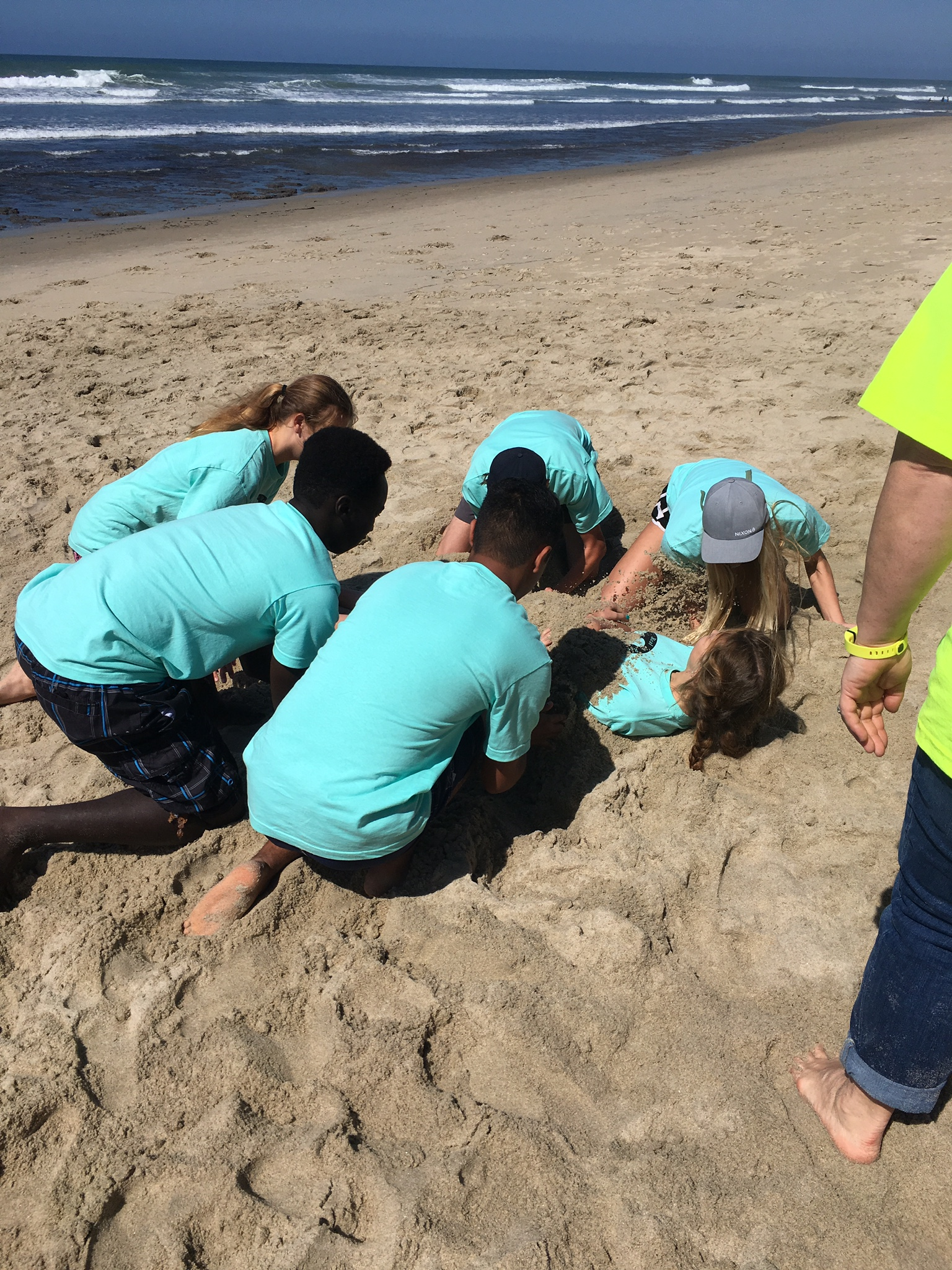 Group working together to bury teamate